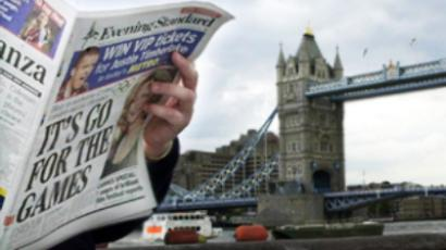 A Londoner reads the Evening Standard near Tower Bridge (AFP Photo / Martyn Hayhow)