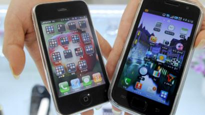 A South Korea shop manager shows Samsung Electronics' Galaxy S mobile phone (R) and Apple's iPhone 3G at a shop in Seoul on July 27, 2010. (AFP Photo/Park Ji-Hwan)