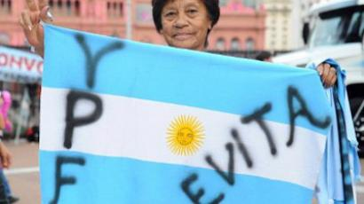 A woman holds an Argentine national flag in front of the presidential palace after Argentine President Cristina Fernandez de Kirchner announced that oil company YPF, controlled by Spain's Repsol, is subject to expropriation and that a bill being introduced would give the state a 51 percent share, in Buenos Aires on April 16, 2012. (AFP Photo / Daniel Garcia)