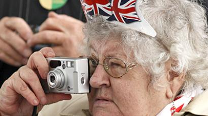 United Kingdom, London: A woman takes a picture during a street party near Tower Bridge during the Thames Diamond Jubilee Pageant on the River Thames in London on June 3, 2012. (AFP Photo / Justin Tallis)