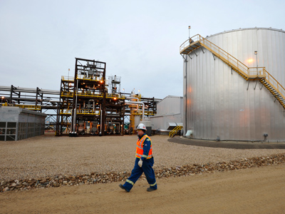 An oilfield worker walks past the Statoil oil sands facility near Conklin, Alberta, Canada (Reuters/Todd Korol)