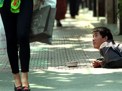 A disabled begger looks at passers-by along street in central Shanghai (AFP Photo/Liu Jin)