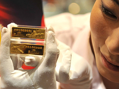 China, Beijing: In a picture taken on June 18, 2012, a worker holds a pair of gold bars to mark the launching of China's Shenzhou-9 spacecraft at a gold shop in Beijing. (AFP Photo)