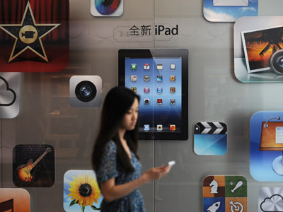 A customer passes an Apple store where the latest version of the Apple iPad went on sale in Apple stores in Shanghai on July 20, 2012. (AFP Photo/Peter Parks)
