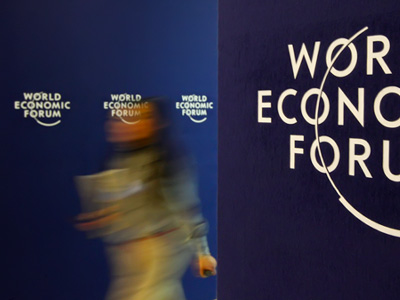 A visitor walks past WEF logo at the venue of the World Economic Forum (WEF) in Davos. (REUTERS/Christian Hartmann)