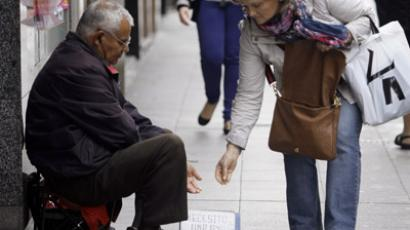 A woman gives money to a beggar on a street in Pontevedra, northwest Spain June 15, 2012. (Reuters/Miguel Vidal)