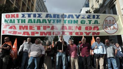 "On strike municipality workers hold a banner reading ""no to layoffs-the measures will not apply"" during a demonstration in central Athens to protest new austerity measures and excpected layoffs in the public sector on November 10, 2012 (AFP Photo / Louisa Gouliamaki)"