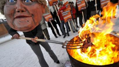 Berlin: An activist dressed up as German Chancellor Angela Merkel throws fake Euro currency notes in a fire during a protest in front of the chancellery building in Berlin. (AFP Photo / John Macdougall)
