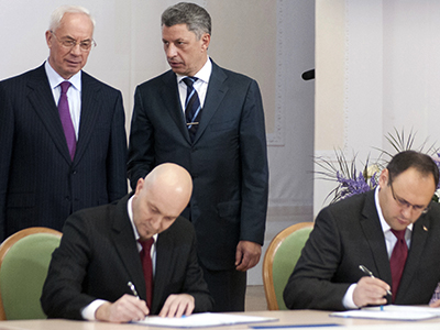Ukrainian Prime Minister Mykola Azarov (L) and Energy Minister Yuri Boiko (2nd R) talk as Vladislav Kaskiv (R), the head of Ukraine's state investment agency, and a man the state investment agency identified as Jordi Sarda Bonvehi (2nd L) sign what the government said was an agreement to build a liquefied natural gas terminal in Ukraine during a meeting in Kiev November 26, 2012. (Reuters)