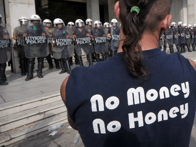 A shipyard worker stands in front of riot policemen guarding the Greek Police headquarters, during a protest to demand the release of some 100 colleagues that were arrested earlier after breaking in to the Defense Ministry in Athens on October 4, 2012.  (AFP Photo/Louisa Gouliamaki)