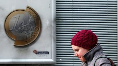"A pedestrian walks by a Eurobank advertisement featuring a one euro coin and the words ""increases (Eurobank) the value of any new deposit"" in Athens February 8, 2012 (Reuters / John Kolesidis)"