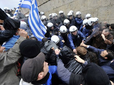 Protesters clash with riot police while they try to enter the parliament during a 24-hours general strike in Athens on February 7, 2012.  (AFP Photo / Louisa Gouliamaki)