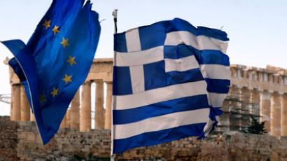 The Parthenon on the Athens Acropolis is seen behind a Greek and an EU flag atop the Greek ministry of finance February 8, 2012 (Reuters / Yannis Behrakis)