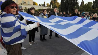 Protesters chant slogans as they hold a large Greek flag during a demonstration against new austerity measures approved by the government, in front of the Parliament in Athens (AFP Photo/Louisa Gouliamaki)