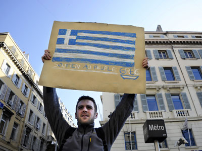 "A man holds a placard bearing the Greek flag and reading ""Support of Greek people"".(AFP Photo / Anne-Christine Poujoulat)"
