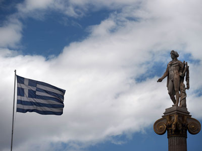 A Greek flag waves next to a statue of the Greek ancient god Apollo in Athens.(AFP Photo / Aris Messinis)