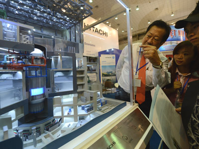 Students look at a model of a nuclear power plant jointly designed by Hitachi and General Electric on display at an international nuclear power exhibition being held in Hanoi on October 26, 2012. (AFP Photo/Hoang Dinh Nam)