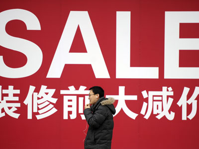 A man walks past a sale poster on a street in Shanghai.(AFP Photo / Peter Parks)
