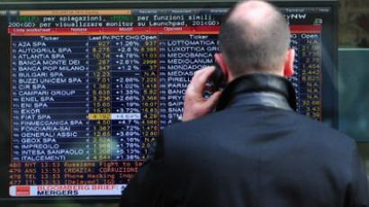 A man looks at a screen displaying index and share prices outside a bank in Milan (AFP Photo / Guiseppe Cacace)