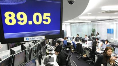 Money dealers work under a foreign currency exchange board in Tokyo (AFP Photo / Jiji Press)