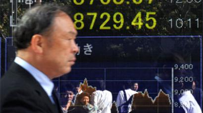 A man walks past a share prices board in Tokyo.(AFP Photo / Kazuhiro Nogi)