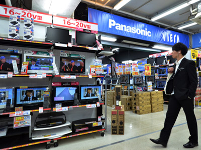 A customer inspects television sets by Japanese electronics manufacturer Panasonic at a store in Tokyo (AFP Photo/Yoshikazu Tsuno)