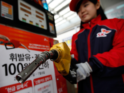 An employee holds a gas pump to refill a car at a petrol station during a photo opportunity (Reuters / Lee Jae Won)