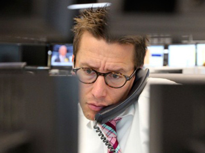 A stock broker works behind computer monitors at the stock exchange in Frankfurt/Main, central Germany, on August 8, 2011 (AFP Photo / Daniel Roland)