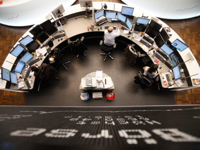 Traders work at their desks below the DAX board at the Frankfurt stock exchange February 1, 2012 (Reuters / Alex Domanski)