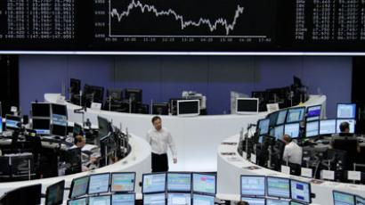 Traders work at their desks in front of the DAX board at the Frankfurt stock exchange.(REUTERS / Thomas Peter)