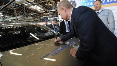 Russian Prime Minister Vladimir Putin, foreground center, signs autograph on the first Lada Largus minivan at the production line launching ceremony at AvtoVAZ car plant in Togliatti, April 4, 2012. (RIA Novosti / Alexsey Druginyn)