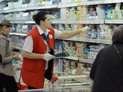 A worker of an Auchan Hypermarket checks dairy products in the shop in Moscow, on October 22, 2012. (AFP Photo/Natalia Kolesnikova)