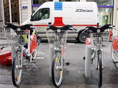 A worker of the French Billboard advertiser JC Decaux repairs a bike in a free cycle station as a Jean-Claude Decaux maintenance van is parked in the street.(AFP Photo / Kenzo Tribouillard)