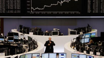 Traders are pictured at their desks in front of the DAX board at the Frankfurt stock exchange.(Reuters / Reuters Staff)
