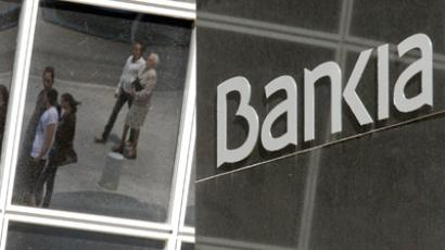 Pedestrians are reflected in the Bankia headquarters building in Madrid May 26, 2012 (Reuters/Andrea Comas)