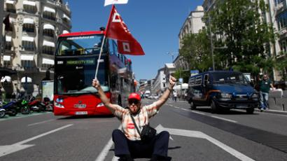 "A man sits on a street as he holds a sign which reads, ""We now need business reform"", during a protest against the labour reform of the Spanish government organized by trade unions near the Spanish parliament in Madrid May 24, 2012 (Reuters/Andrea Comas)"