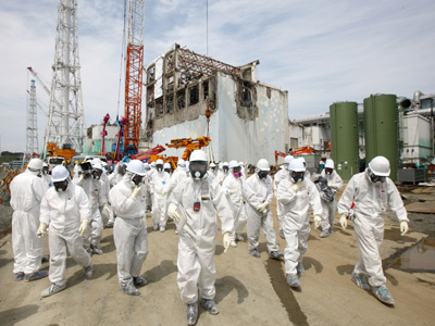 Members of the media and Tokyo Electric Power Co. (Tepco) employees look at the No. 4 reactor building (rear), amongst tsunamai damage, at the company's Fukushima Dai-Ichi nuclear power plant in Okuma Town, Fukushima Prefecture (AFP Photo / Tomohiro Ohsumi)
