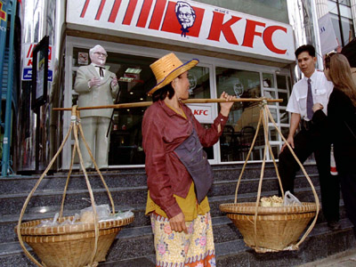 A Thai woman carries street food as she stops in front of a Kentucky Fried Chicken restaurant (Reuters / Patrick de Noirmont)