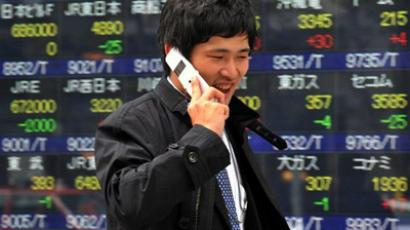 A businessman uses his mobile phone before a share prices board in Tokyo (AFP Photo / Yoshikazu Tsuno)