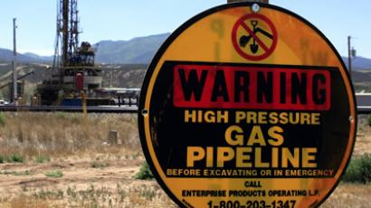 A drilling rig operates as a sign warns of underground natural gas pipelines outside Rifle, Colorado, June 6, 2012. (Reuters/George Frey)