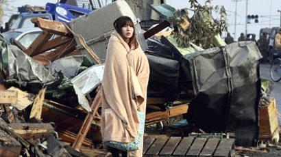 Japan, Ishinomaki: A girl, wrapped in a blanket, stands to look on tsunami damaged town at Ishinomaki city in Miyagi prefecture on March 13, 2011. (AFP Photo / Yomiuri Shimbnun)