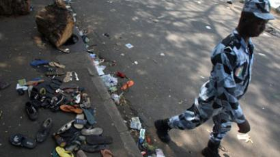 A man walks in a street as shoes are scattered on the pavement at the scene of a stampede in Abidjan.(AFP Photo / Herve Sevi)