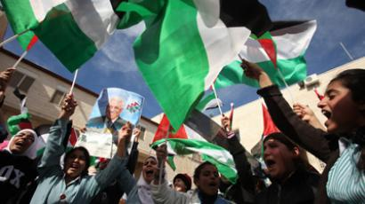 Palestinian students wave their flag following a speech by President Mahmud Abbas at his headquarters in the West Bank city of Ramallah, on November 25, 2012 (AFP Photo / Abbas Momani)