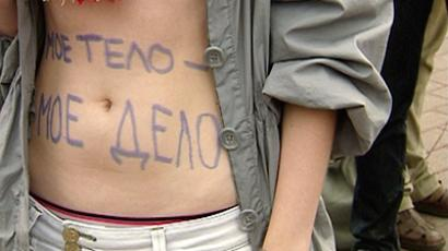 """My body is my business"" reads the slogan which a protestor against abortion restrictions has written on her stomach"