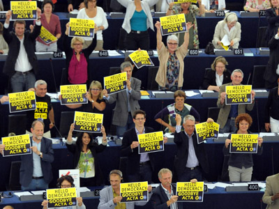 "Members of the European Parliament hold placard reading ""Hello democracy goodbye ACTA"" as they take part in a vote on Anti-Counterfeiting Trade Agreement (ACTA) at the European Parliament in Strasbourg, eastern France, on July 04, 2012. (AFP Photo/Frederick Florin)"