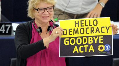 "Eva Joly (up) hold placard reading ""Hello democracy goodbye ACTA"" at the European Parliament in Strasbourg, eastern France, on July 04, 2012 (AFP Photo/Frederick Florin)"