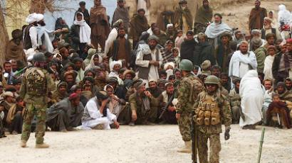 Afghan National Army soldiers keep watch as Afghans gather outside a U.S. base in Panjwai district Kandahar province, March 11, 2012 (Reuters / Ahmad Nadeem)