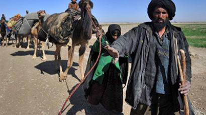 An Afghan man with his family carry their camels in Gamser, southern Afghanistan (AFP Photo / Adek Berry)