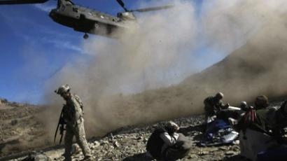 US Army soldiers from 2-506 Infantry 101st Airborne Division and Afghan National Policemen and Army take cover from dust and debris from a UH-47 Chinook helicopter (AFP Photo / DAVID FURST)