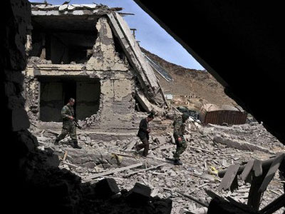 Afghanistan security forces and International Security Assistance Force (ISAF) officials walk through debris  (AFP Photo/Massoud Hossaini)